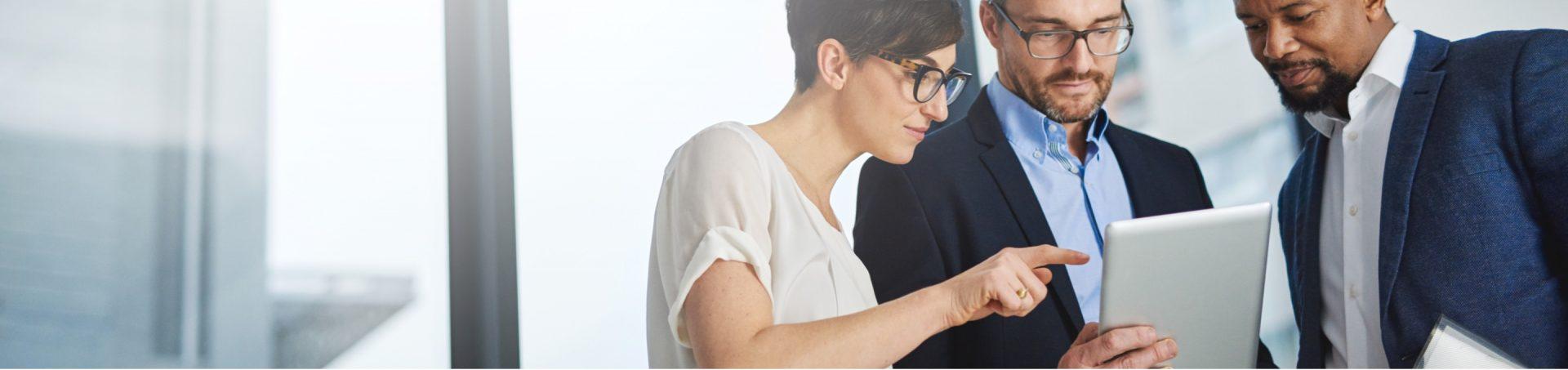 Deux hommes et une femme devant une tablette