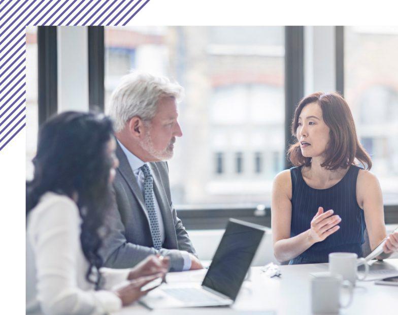 Un homme et deux femmes discutent autour d'un table