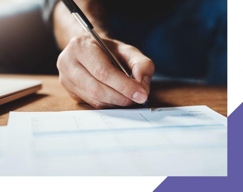 Une main en train d'écrire sur une feuille